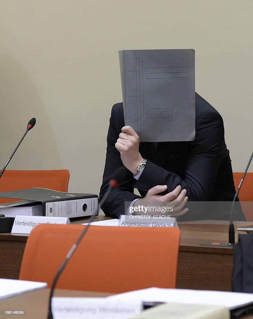 Co-defendant Holger Gerlach hides his face behind a folder at the start of the trial of Beate Zschaepe, charged with complicity in the murders of eight ethnic Turks, a Greek immigrant and a German policewoman between 2000 and 2007 as a founding member and sole survivor of the far-right gang dubbed the National Socialist Underground (NSU), at a Munich courthouse, southern Germany, on May 6, 2013. STACHE