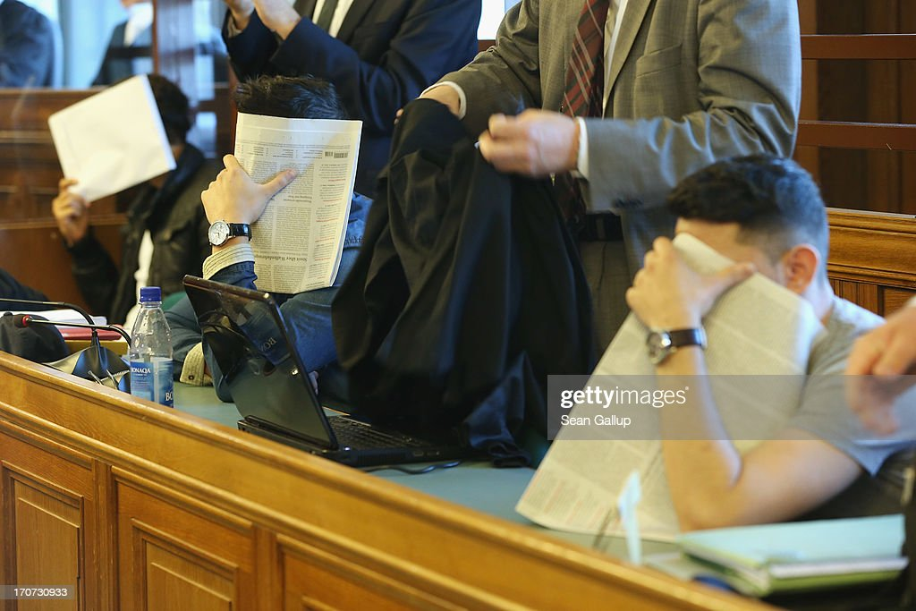 Co-defendants cover their faces shortly before the continuation of the trial of the six Jonny K. attackers at the Kriminalgericht Moabit court on June 17, 2013 in Berlin, Germany. The six young men are accused of assaulting Jonny K. in front of a bar on Alexanderplatz on October 14, 2012, and beating him so severely that Jonny K. later died of his head injuries. His sister Tina has led a media campaign to draw publicity to the case and the issue of violence in German society.