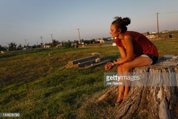 Codessa Schoonover spends time remembering her grandmother as she sits on what remains of the tree in front of the home her grandmother was killed in...