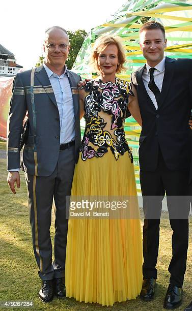 CoDirector of the Serpentine Gallery HansUlrich Obrist and Julia PeytonJones pose with Simon Denny at The Serpentine Gallery summer party at The...