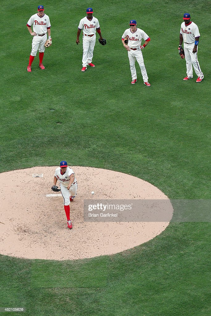 Cody Asche #25, Jimmy Rollins #11, Chase Utley #26 and Ryan Howard #6 all of the Philadelphia Phillies look on as Mario Hollands #43 warms up in the sixth inning of the game against the Washington Nationals at Citizens Bank Park on July 13, 2014 in Philadelphia, Pennsylvania.