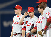 Cody Asche of the Philadelphia Phillies and Jayson Nix and Chase Utley and John Mayberry Jr #15 look on during a pitching change during MLB game...
