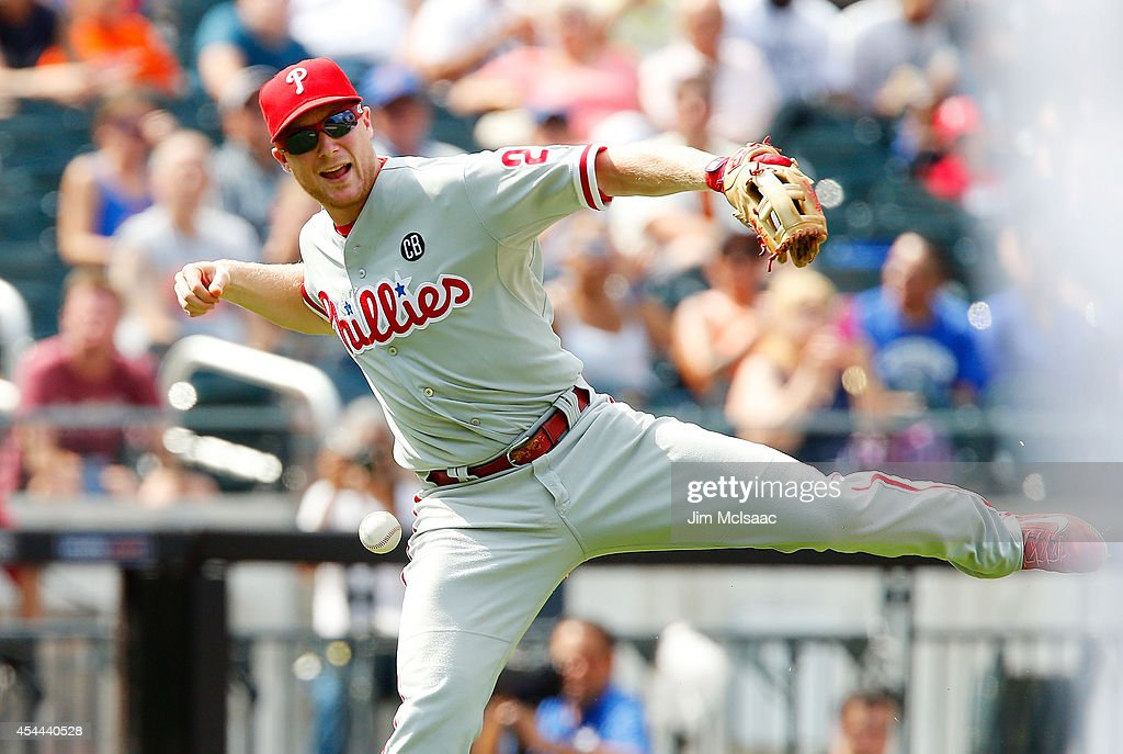Cody Asche #25 of the Philadelphia Phillies can't handle a ball hit for a fourth inning infield single by Wilmer Flores #4 of the New York Mets at Citi Field on August 31, 2014 in the Flushing neighborhood of the Queens borough of New York City.