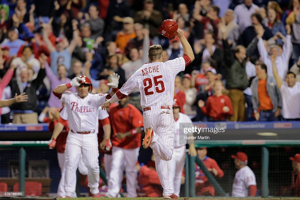 Cody Asche of the Philadelphia Phillies celebrates as he scores the winning run in the eleventh inning during a game against the Cincinnati Reds at...
