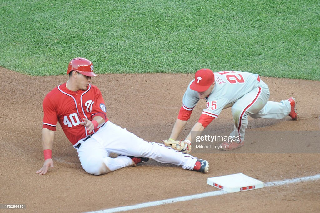 Cody Asche #25 of the Philadelphia Phillies tages out <a gi-track='captionPersonalityLinkClicked' href=/galleries/search?phrase=Wilson+Ramos&family=editorial&specificpeople=4866956 ng-click='$event.stopPropagation()'>Wilson Ramos</a> #40 of the Washington Nationals at third base during a baseball game on August 11, 2013 at Nationals Park in Washington, DC. The Nationals won 6-0.