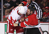 Cody Bass of the Chicago Blackhawks and Aaron Rome of the Detroit Red Wings fight in the second period during a preseason game at the United Center...