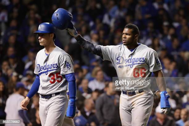 Cody Bellinger and Yasiel Puig of the Los Angeles Dodgers celebrate after scoring runs in the fourth inning against the Chicago Cubs during game five...