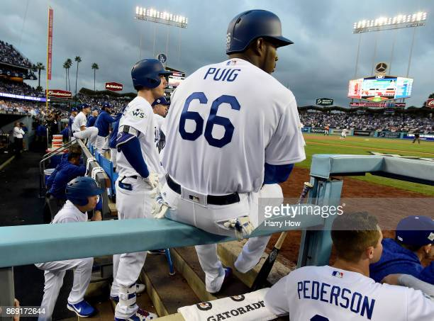 Cody Bellinger and Yasiel Puig of the Los Angeles Dodgers look on from the dugout during the first inning against the Houston Astros in game seven of...