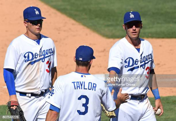 Cody Bellinger is greeted by Joc Pederson and Chris Taylor of the Los Angeles Dodgers after making a diving catch in the seventh inning of the game...