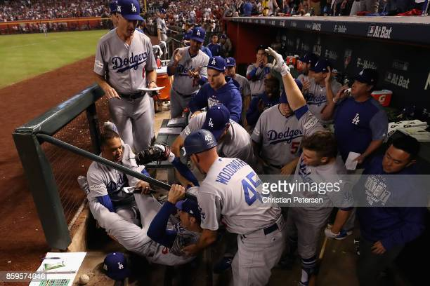 Cody Bellinger of the Los Angeles Dodgers falls into the dugout over manager Dave Roberts and third base coach Chris Woodward after catching a foul...