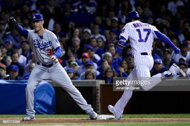 Cody Bellinger of the Los Angeles Dodgers forces out Kris Bryant of the Chicago Cubs at first base in the first inning during game five of the...
