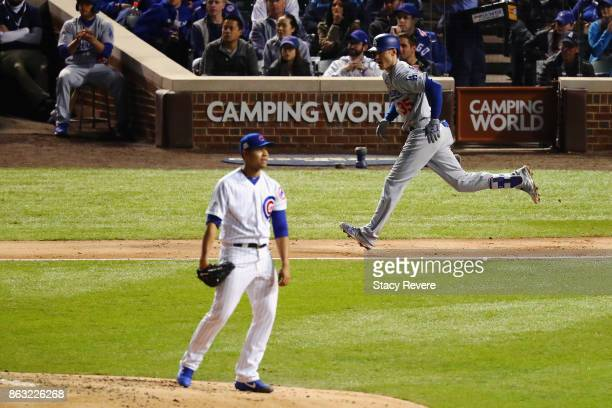 Cody Bellinger of the Los Angeles Dodgers hits a single as Jose Quintana of the Chicago Cubs looks on in the third inning during game five of the...