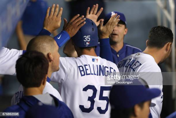Cody Bellinger of the Los Angeles Dodgers is congratulated by teammates after scoring in the second inning on a single to left field by teammate Alex...