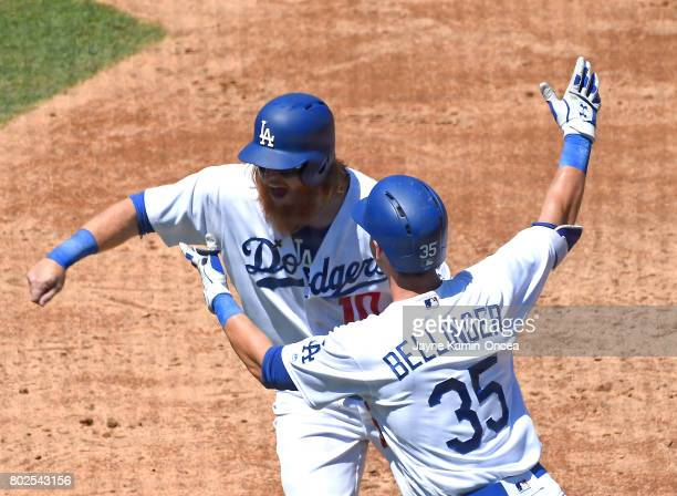 Cody Bellinger of the Los Angeles Dodgers is greeted by Justin Turner after hitting a two run home run in the game against the Colorado Rockies at...