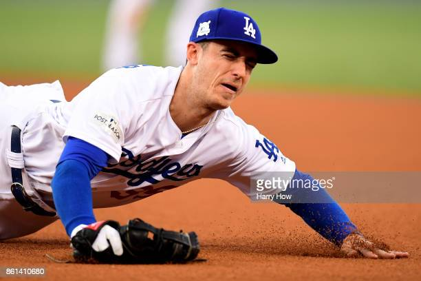 Cody Bellinger of the Los Angeles Dodgers misses a ball hits a by Jose Quintana of the Chicago Cubs during the third inning in Game One of the...