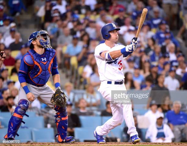 Cody Bellinger of the Los Angeles Dodgers reacts to his solo homerun in front of Travis d'Arnaud of the New York Mets his second homerun of the game...