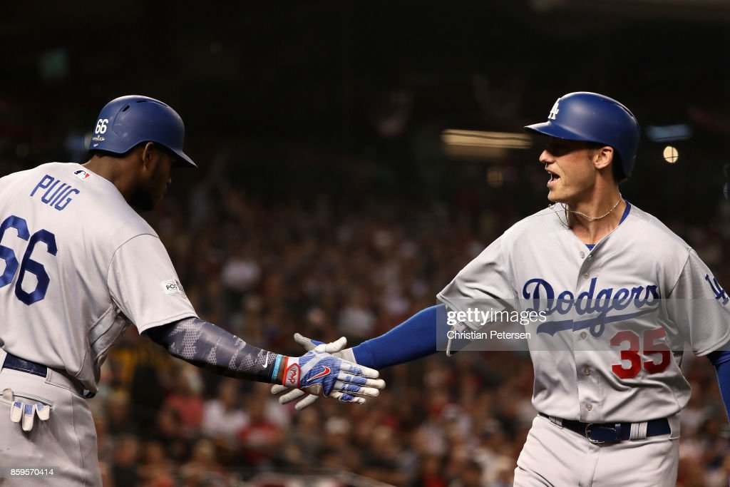 Cody Bellinger #35 of the Los Angeles Dodgers reacts with team mate Yasiel Puig #66 after hitting a one run home run during the fifth inning of the National League Divisional Series game three against the Arizona Diamondbacks at Chase Field on October 9, 2017 in Phoenix, Arizona.