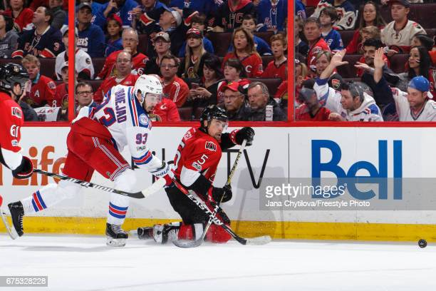 Cody Ceci of the Ottawa Senators clears the puck from his knees as Mika Zibanejad of the New York Rangers skates for the puck in Game Two of the...