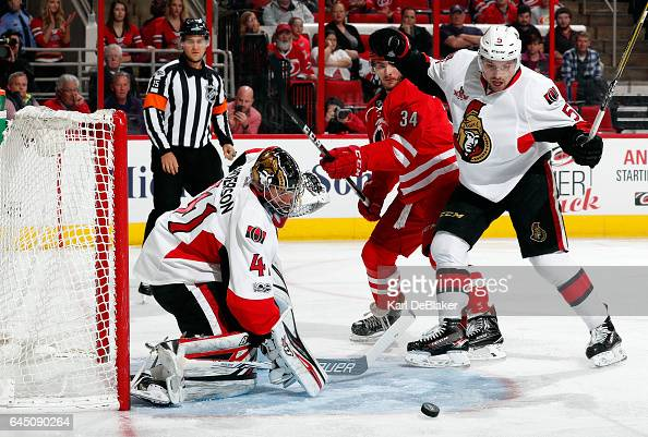 Cody Ceci of the Ottawa Senators keeps Phillip Di Giuseppe outside of the crease as Craig Anderson watches a shot careen wide of the net during an...