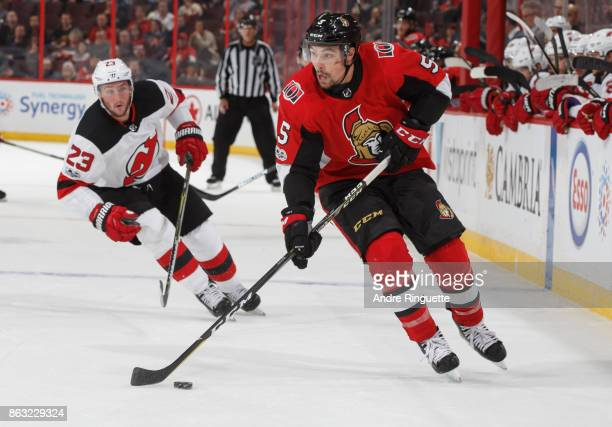 Cody Ceci of the Ottawa Senators stickhandles the puck as Stefan Noesen of the New Jersey Devils pressures on the forecheck at Canadian Tire Centre...