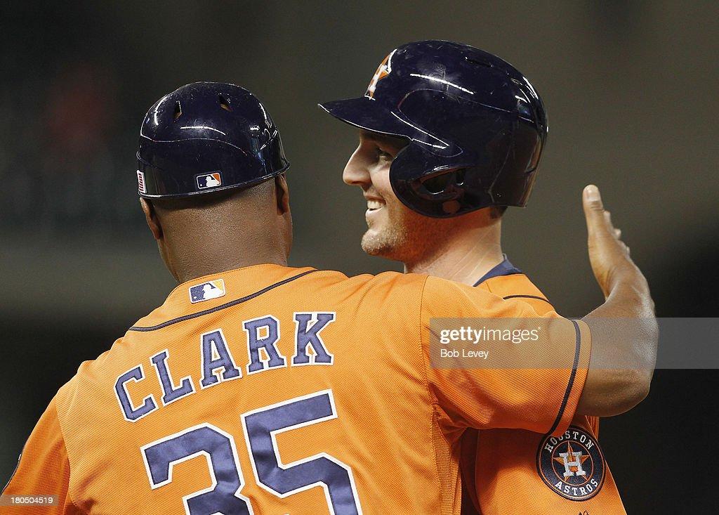 Cody Clark #39 of the Houston Astros is congratulated by first base coach Dave Clark after getting his first major league hit in the fifth inning against the Los Angeles Angels of Anaheim at Minute Maid Park on September 13, 2013 in Houston, Texas.
