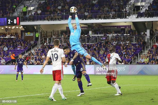 Cody Cropper of New England Revolution leaps over Dom Dwyer of Orlando City SC to make a save during a MLS soccer match at Orlando City Stadium on...