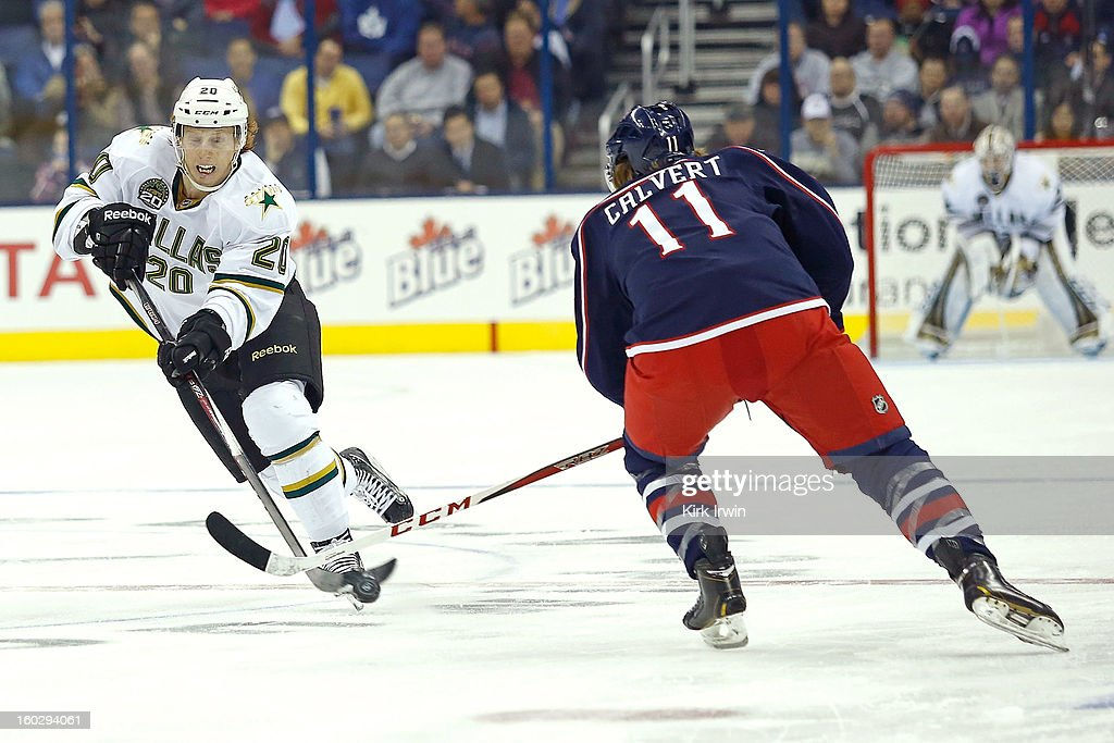 Cody Eakin #20 of the Dallas Stars flips the puck past Matt Calvert #11 of the Columbus Blue Jackets during the first period on January 28, 2013 at Nationwide Arena in Columbus, Ohio.