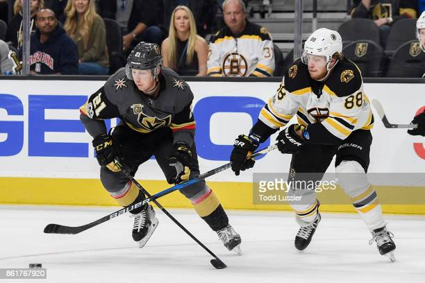 Cody Eakin of the Vegas Golden Knights and David Pastrnak of the Boston Bruins skate to the puck during the game at TMobile Arena on October 15 2017...