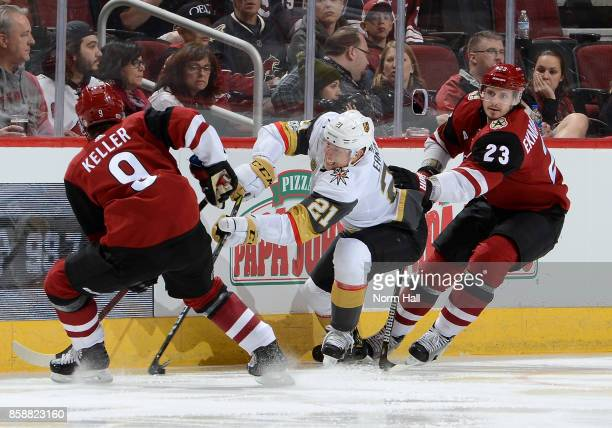 Cody Eakin of the Vegas Golden Knights battles for the puck between Clayton Keller and Oliver EkmanLarsson of the Arizona Coyotes during the second...