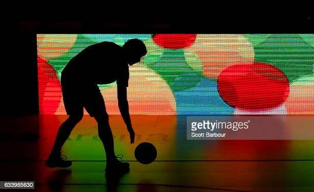 Cody Ellis of the Illawarra Hawks is silhouetted by an electronic advertising board as he warms up prior to the round 18 NBL match between Melbourne...
