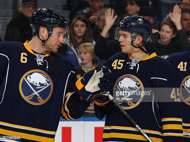 Cody Franson and Brendan Guhle of the Buffalo Sabres talk while warming up before playng the Boston Bruins in an NHL game at the KeyBank Center on...