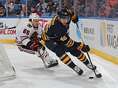 Cody Franson of the Buffalo Sabres controls the puck against Andrew Shaw of the Chicago Blackhawks during an NHL game on December 19 2015 at the...