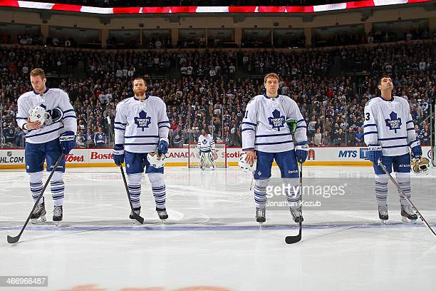Cody Franson Tim Gleason Nikolai Kulemin and Nazem Kadri of the Toronto Maple Leafs stand on the ice during the singing of 'O Canada' prior to puck...