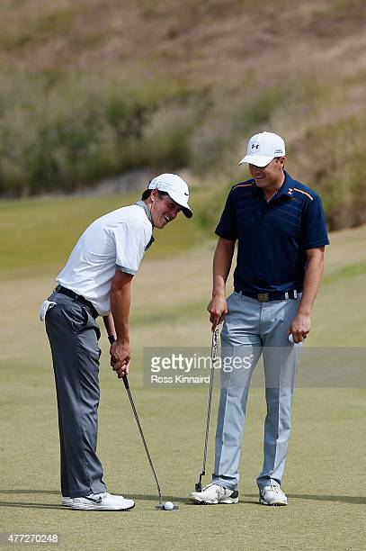 Cody Gribble of the United States and Jordan Spieth of the United States laugh on a green during a practice round prior to the start of the 115th US...
