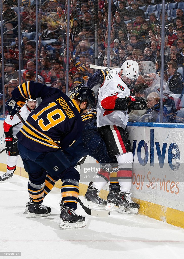 Cody Hodgson #19 and Christian Ehrhoff #10 of the Buffalo Sabres battle for the puck along the boards with Marc Methot #3 of the Ottawa Senators as Bobby Ryan #6 of Ottawa follows the play at First Niagara Center on December 10, 2013 in Buffalo, New York.
