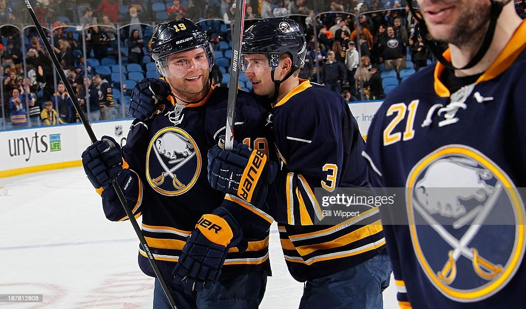 Cody Hodgson #19 and Mark Pysyk #3 of the Buffalo Sabres celebrate their 3-2 shootout victory over the Los Angeles Kings on November 12, 2013 at the First Niagara Center in Buffalo, New York.
