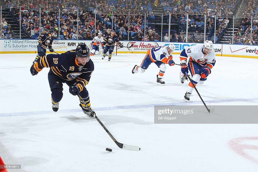 Cody Hodgson #19 of the Buffalo Sabres brings the puck up ice chased by Andrew MacDonald #47 of the New York Islanders on April 26, 2013 at the First Niagara Center in Buffalo, New York.