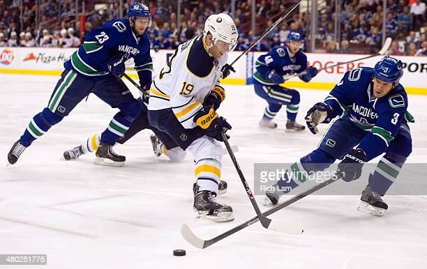 Cody Hodgson of the Buffalo Sabres looses the puck after getting checked by Kevin Bieksa of the Vancouver Canucks during the first period in NHL...