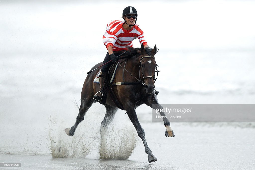 Cody is ridden through the water in the Wairarapa Station Hack Race during the Castlepoint Beach Races at Castlepoint Beach on March 2, 2013 in Masterton, New Zealand.
