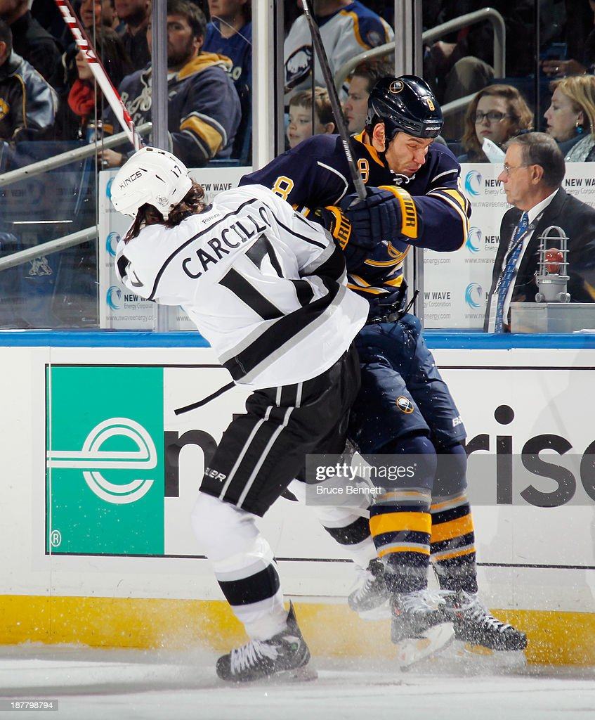 Cody McCormick #8 of the Buffalo Sabres is checked by Daniel Carcillo #17 of the Los Angeles Kings during the first period at the First Niagara Center on November 12, 2013 in Buffalo, New York.
