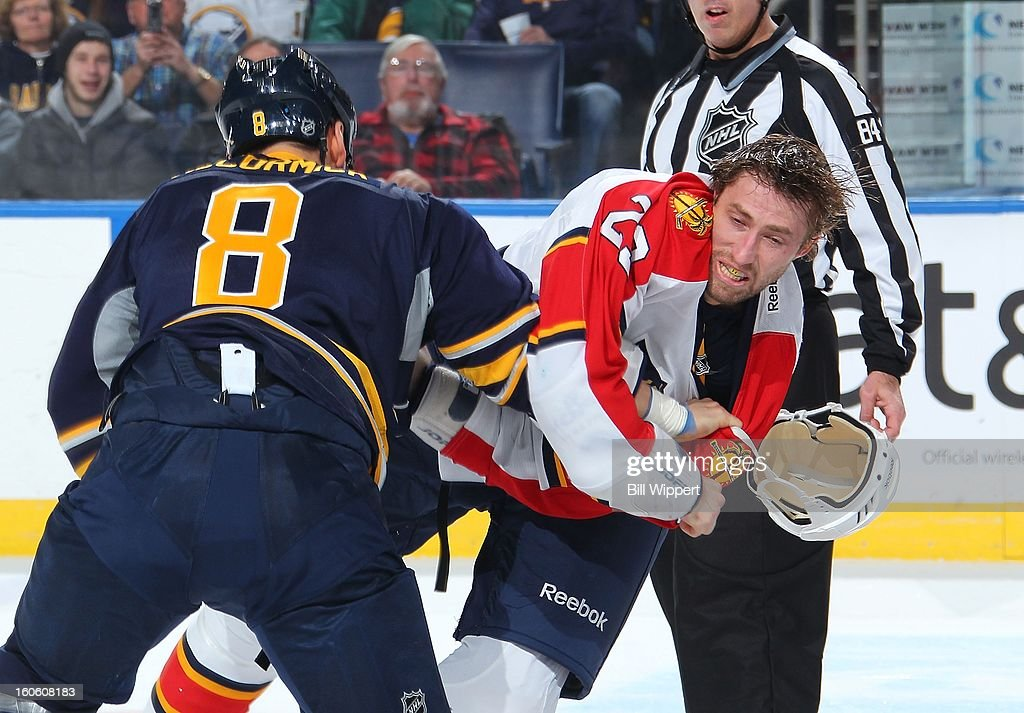 Cody McCormick #8 of the Buffalo Sabres knocks the helmet of Tyson Strachan #23 of the Florida Panthers off with a punch on February 3, 2013 at the First Niagara Center in Buffalo, New York.