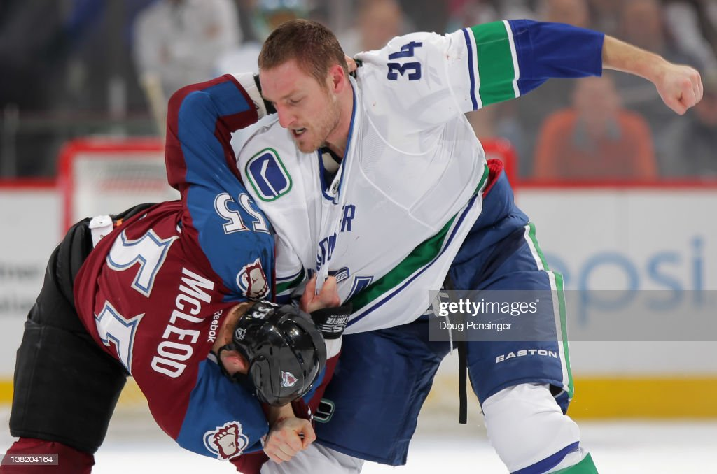 Cody McLeod of the Colaorado Avalanche and Byron Bitz of the Vancouver Canucks engage in a fight in the first period at the Pepsi Center on February...