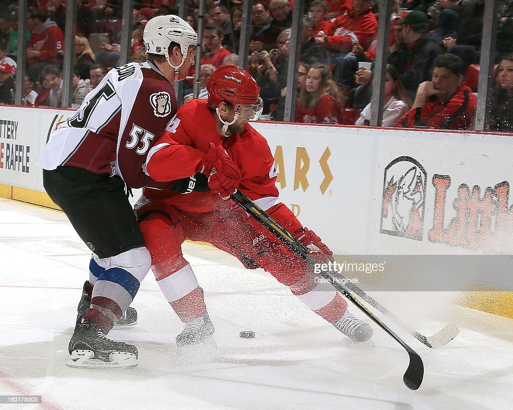 Cody McLeod #55 of the Colorado Avalanche and Jakub Kindl #4 of the Detroit Red Wings go hard into the corner for the puck during a NHL game at Joe Louis Arena on March 5, 2013 in Detroit, Michigan.