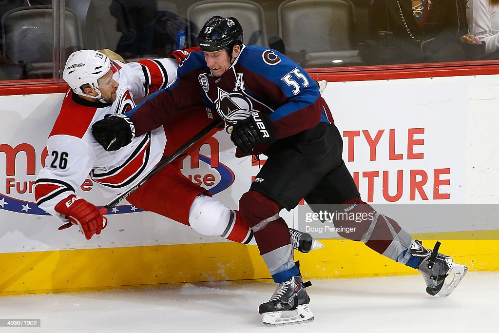 Cody McLeod of the Colorado Avalanche puts a hit on JohnMichael Liles of the Carolina Hurricanes in the third period at Pepsi Center on October 21...