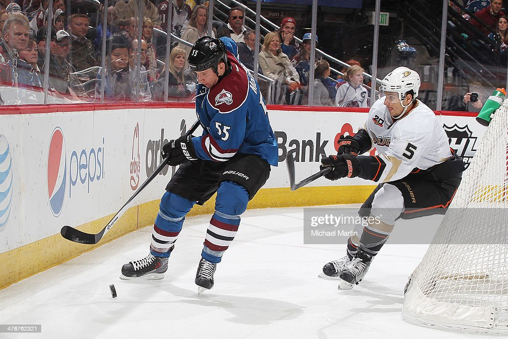 Cody McLeod #55 of the Colorado Avalanche skates with the puck against Luca Sbisa #5 of the Anaheim Ducks at the Pepsi Center on March 14, 2014 in Denver, Colorado.