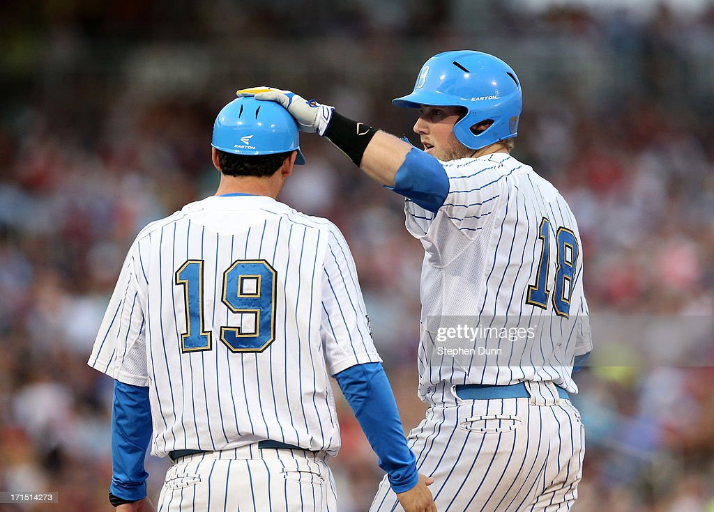 Cody Regis #18 of the UCLA Bruins pats first base coach Jake Silverman #19 on the head after hitting an RBI single in the fourth inning against the Mississippi State Bulldogs during game two of the College World Series Finals on June 25, 2013 at TD Ameritrade Park in Omaha, Nebraska.