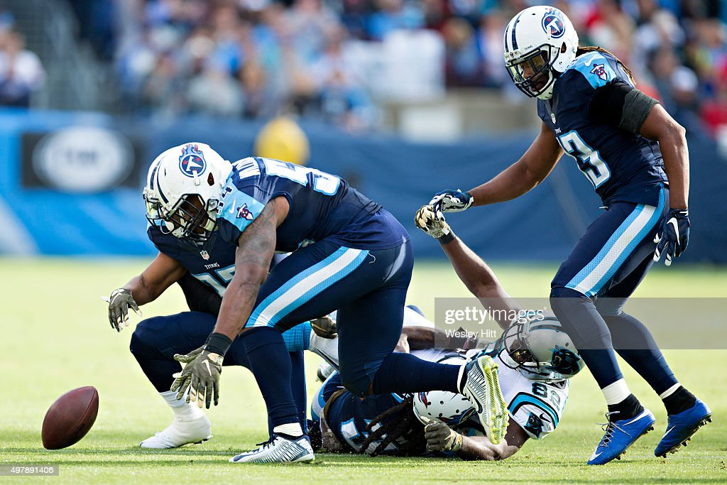 Cody Riggs #37, Avery Williamson #54 and B.W. Webb #38 of the Tennessee Titans tackle Jerricho Cotchery #82 of the Carolina Panthers and force a fumble at Nissan Stadium on November 15, 2015 in Nashville, Tennessee.