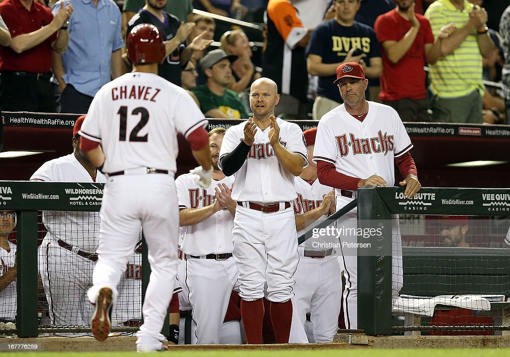 Cody Ross #7 and manager Kirk Gibson #23 of the Arizona Diamondbacks congratulate Eric Chavez #12 after Chavez hit a solo home run against the San Francisco Giants during the fourth inning of the MLB game at Chase Field on April 29, 2013 in Phoenix, Arizona.