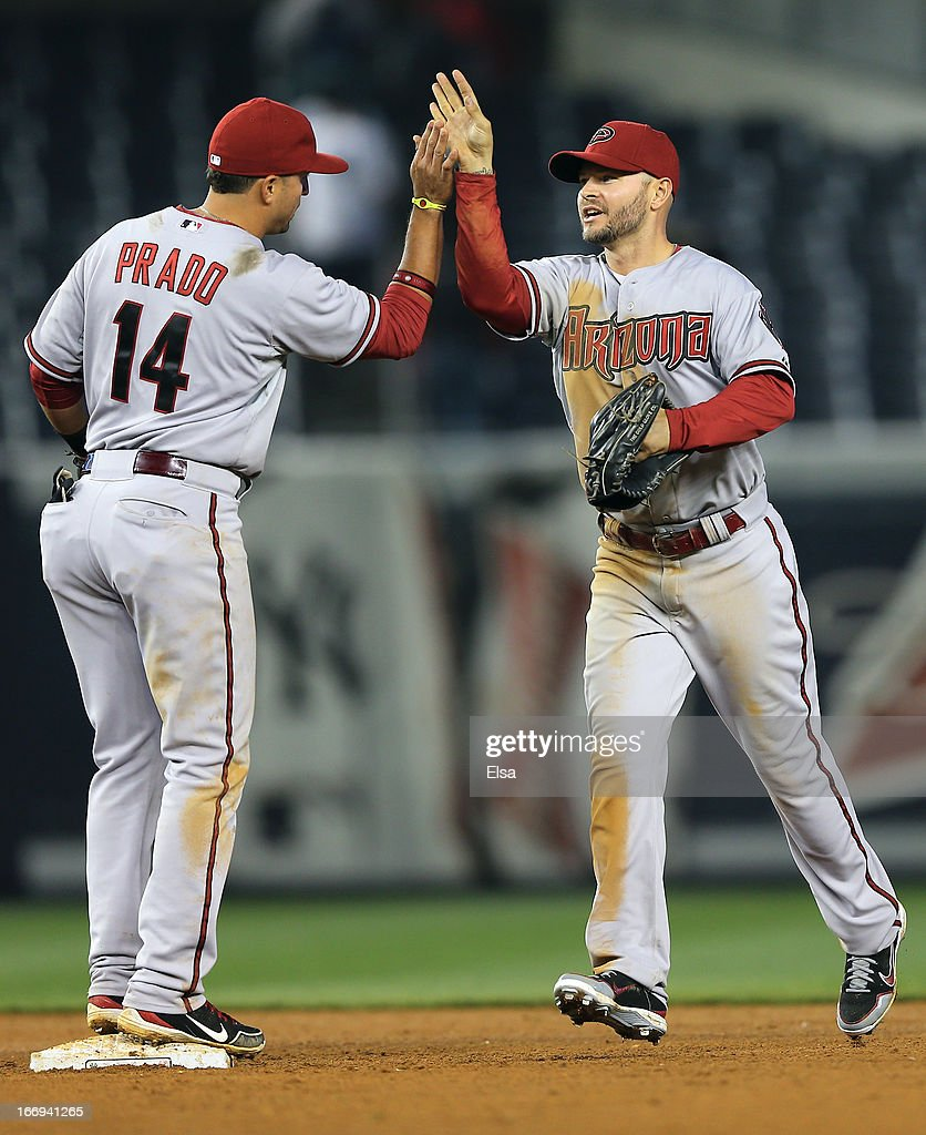 Cody Ross #7 and Martin Prado #14 of the Arizona Diamondbacks celebrate the win over the New York Yankees on April 18, 2013 at Yankee Stadium in the Bronx borough of New York City.The Arizona Diamondbacks defeated the New York Yankees 6-2 in 12 innings.
