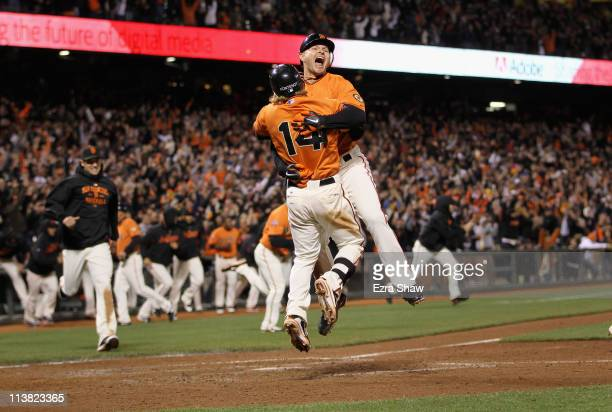 Cody Ross and Mike Fontenot of the San Francisco Giants celebrate after Ross scored the winning run on a hit by Freddy Sanchez in the bottom of the...